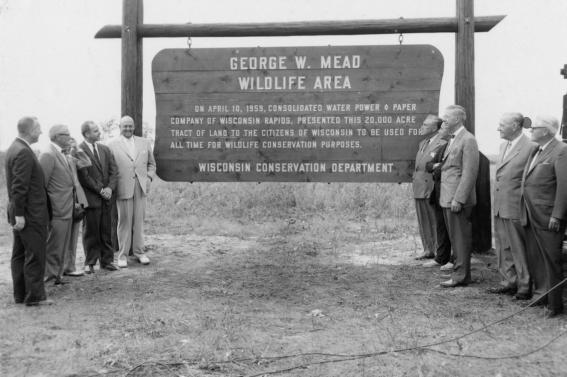 Historic black and white photo showing group of men gathered around large sign that reads George W. Mead Wildlife Area