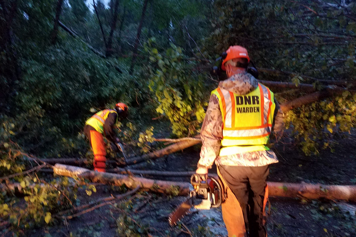 Photo of DNR personnel in reflective vests helping clear brush