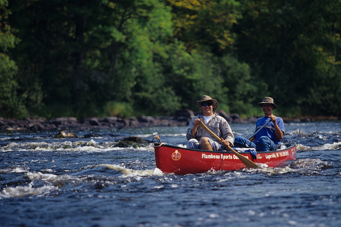 Two men in red canoe paddling in fast-moving river