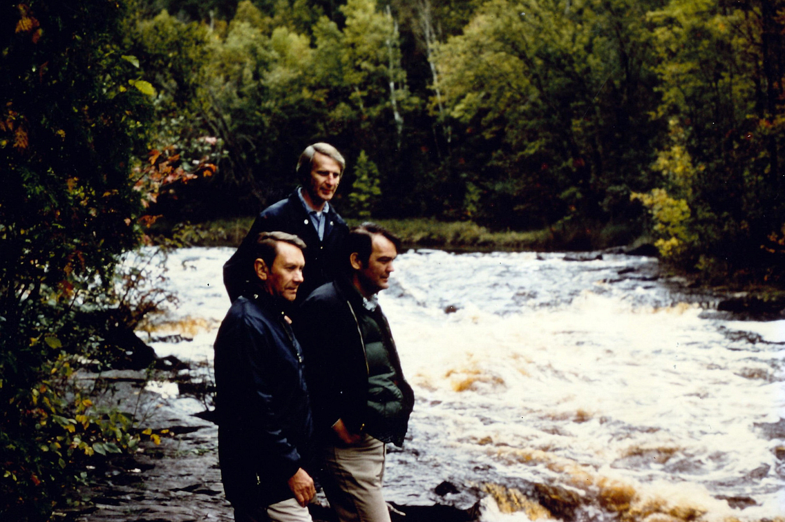 Three men standing near a waterfall