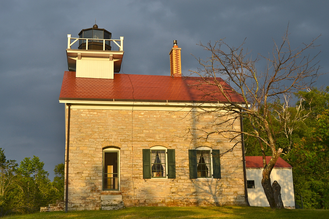 Cream-colored brick building with red roof and lighthouse on roof