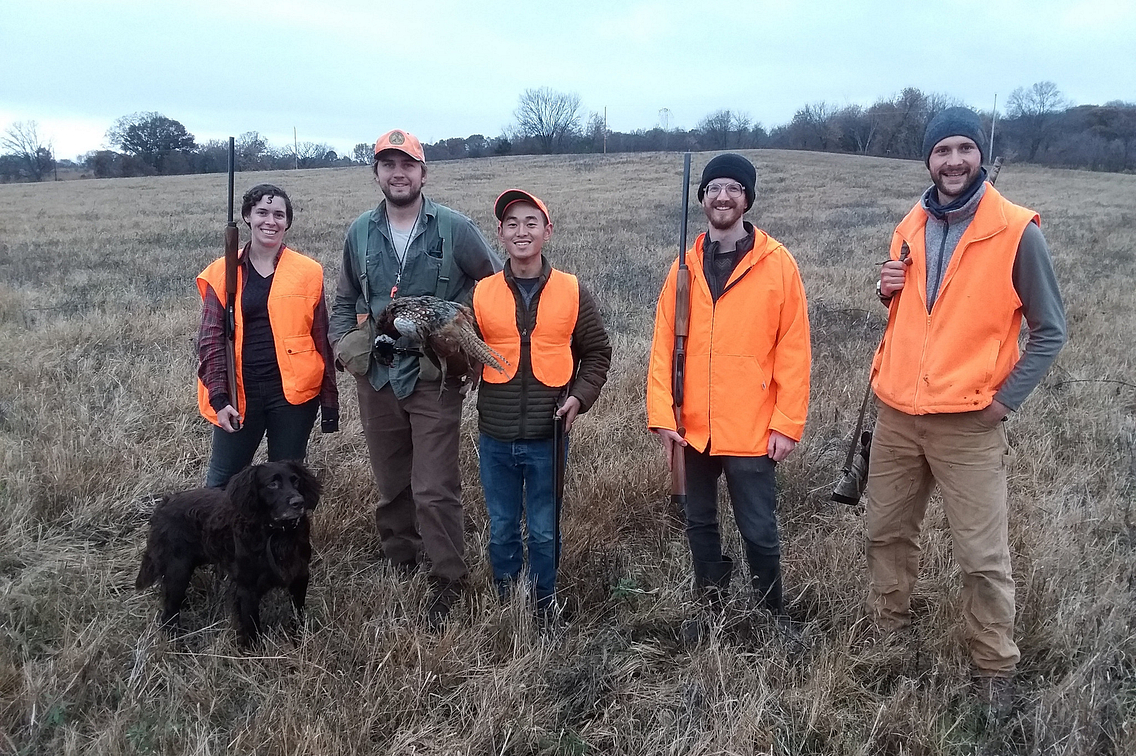 Group of hunters standing in field, with a dog.