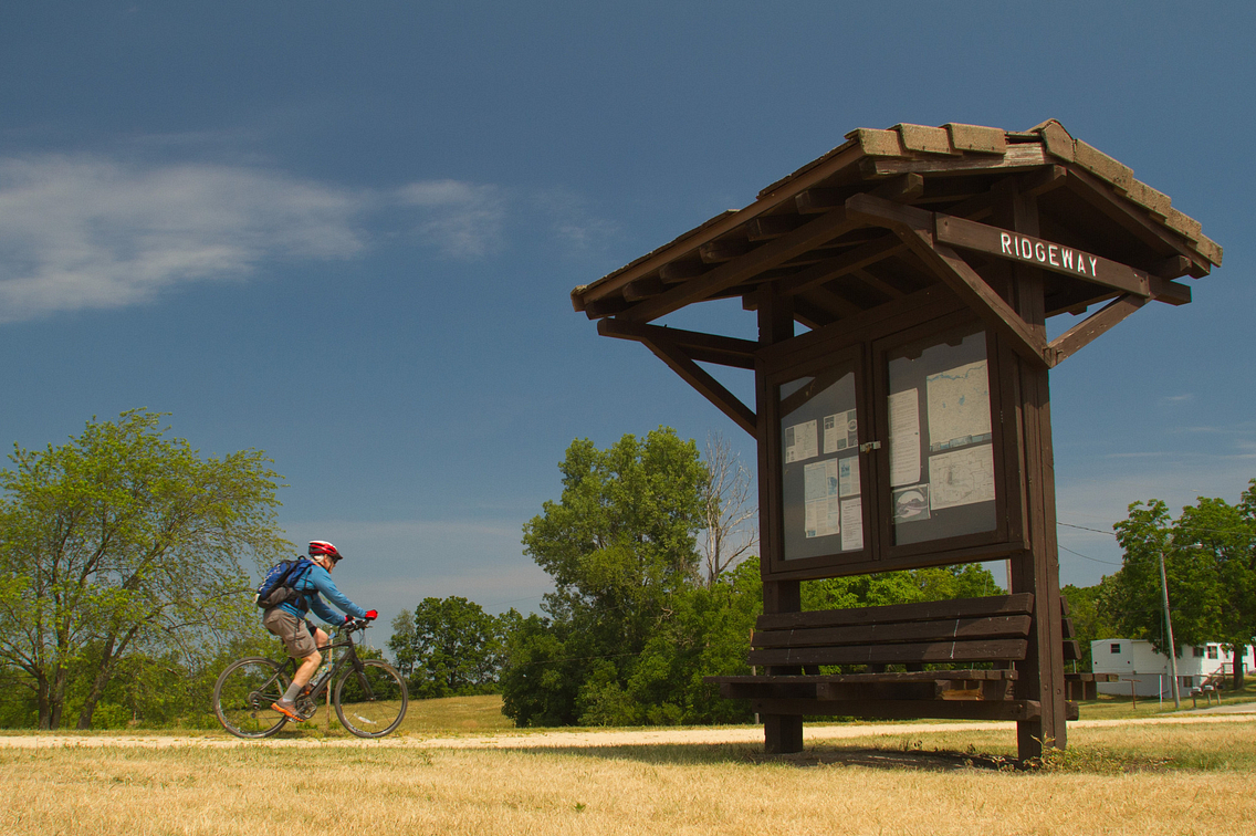 A bicyclist rides the Military Ridge State Trail near a kiosk that reads Ridgeway