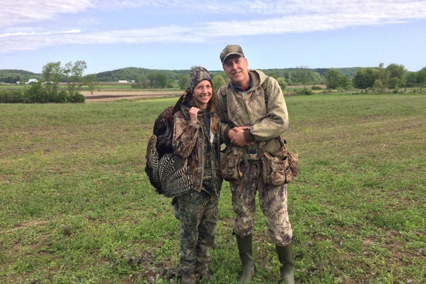 Two hunters in hunting clothing, standing in a field. Woman hunter on left carries a turkey she shot.