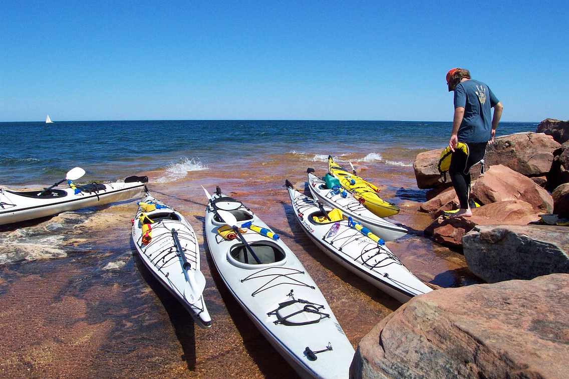 Sea kayaks are lined up on shore of Lake Superior with blue sky and blue water