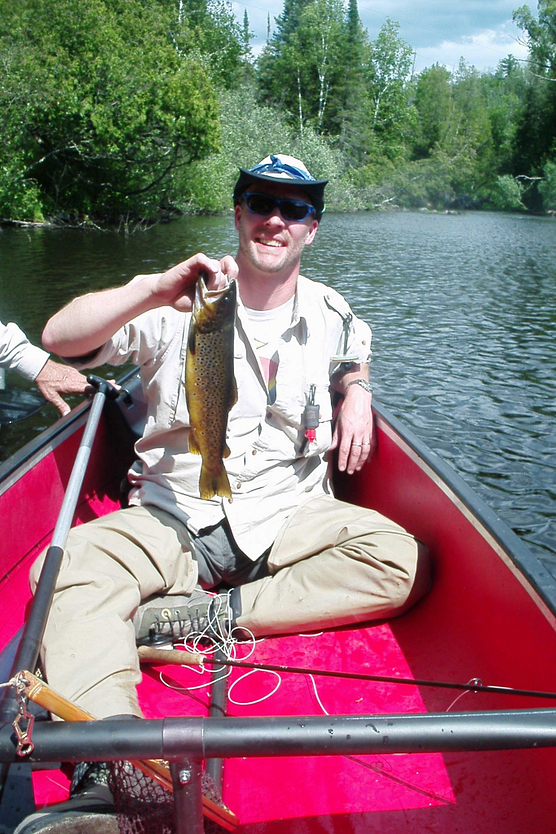 Man in a canoe with a big smile, holding trout he caught