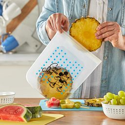 Woman placing pineapple in Half Gallon (2-qt) Silicone Storage Bag: Disney Mickey Mouse