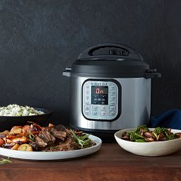 Instant Pot® Duo™ 6-quart Multi-Use Pressure Cooker with food in bowls on the table