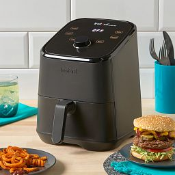 Instant™ Vortex™ Mini 2-quart Air Fryer, Black on the counter with a hamburg on the a plate beside it