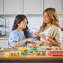 Mom and daughter putting food in 8-pc Mickey & Friends Glass storage set