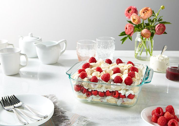 Eton Mess layered raspberry dessert shown in an 8 x 8 Pyrex baking dish on a table setting with flowers