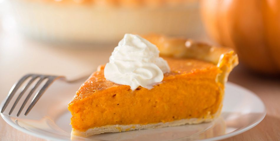Pumpkin pie with whipped cream dollup on white plate with fork
