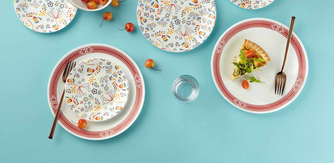 Prairie Garden red pattern featuring a full-coverage floral pattern on salad plates and a red rim on dinnerware plates