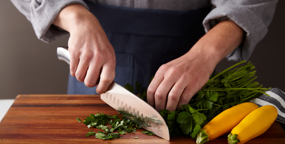 Person using a belmont chicago cutlery knife to chop herbs on a cutting board