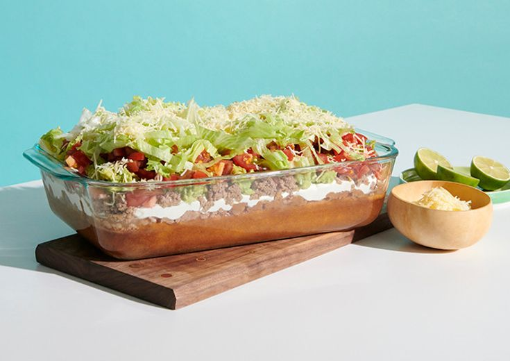 Pyrex deep baking dish with layered dip on table