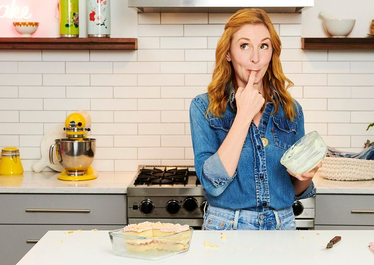 Christina Tosi eating frosting out of a Pyrex decorated storage dish with a Strawberry Lemon cake on the
