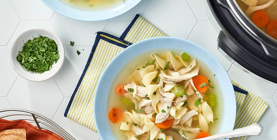 Chicken noodle soup in bowls on the table.