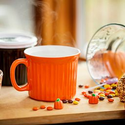 Colours® Pop-Ins® Vermilion 20-oz Mug w/ Lid in a autumn setting with steam rising from the top