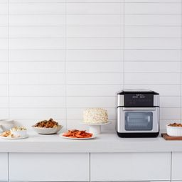 Instant Vortex Pro 10-quart Air Fryer Oven on the counter with various foods