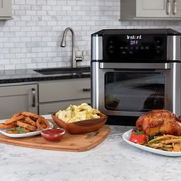 Instant Vortex Plus 10-quart Air Fryer Oven on the counter with chicken, onion rings and other food