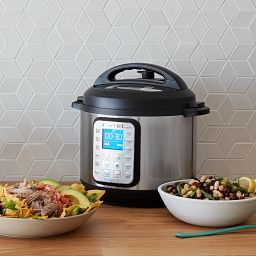 Instant Pot® Smart Wifi 6-quart Multi-Use Pressure Cooker and WiFi Compatible image on the table with dishes of food beside it
