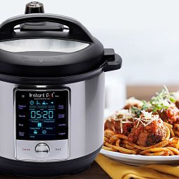Instant Pot  Max Multi-Use 6-quart Pressure Cooker with plate of spaghetti on the table beside it