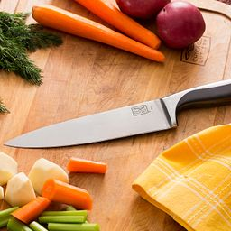 Knife on cutting board with vegetables