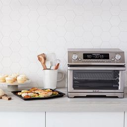 Instant™ Omni™ Plus 26 Litre Toaster Oven and Air Fryer with food on tray on the counter