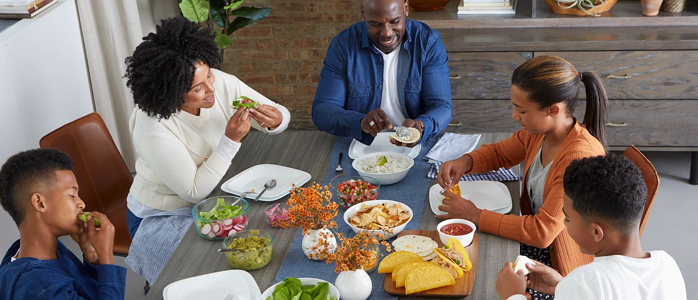 Family eating tacos around dinner table on corelle plates
