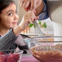 Young girl helping to whisk up brownies in a 2.5-qt mixing bowl