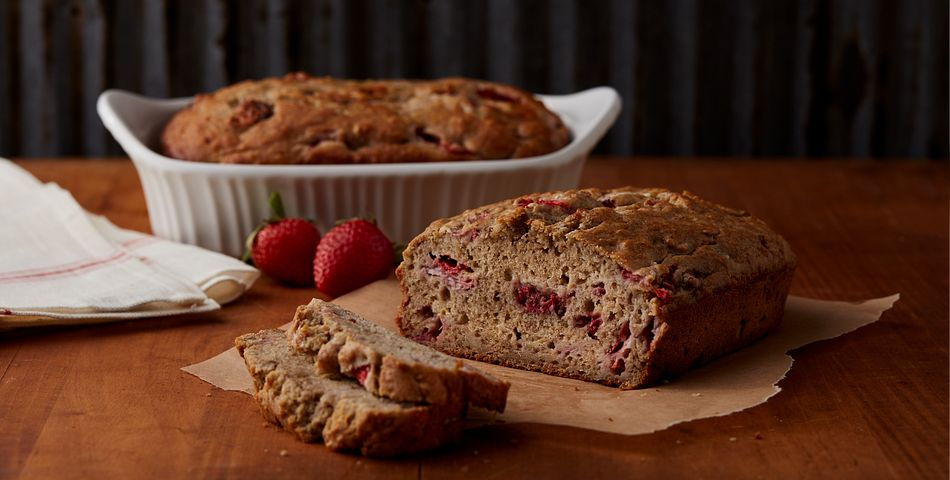 Strawberry Banana Bread on table with loaf fliced open showing pieces