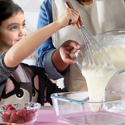 1.5-quart Mixing Bowl with little girl helping to pour batter out of bowl
